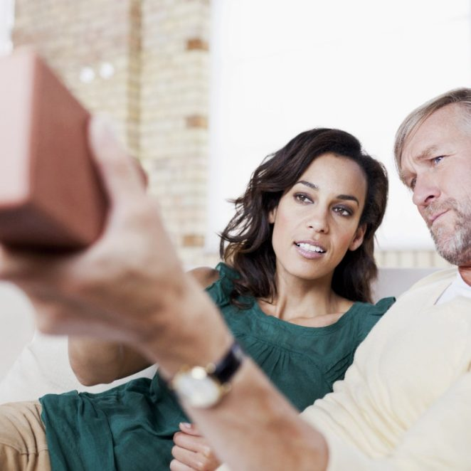 Woman and man on sofa inspecting a clay brick in front of brick-built wall